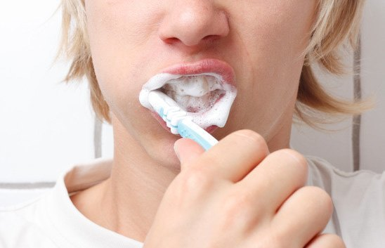 brushing teeth with an sls free toothpaste